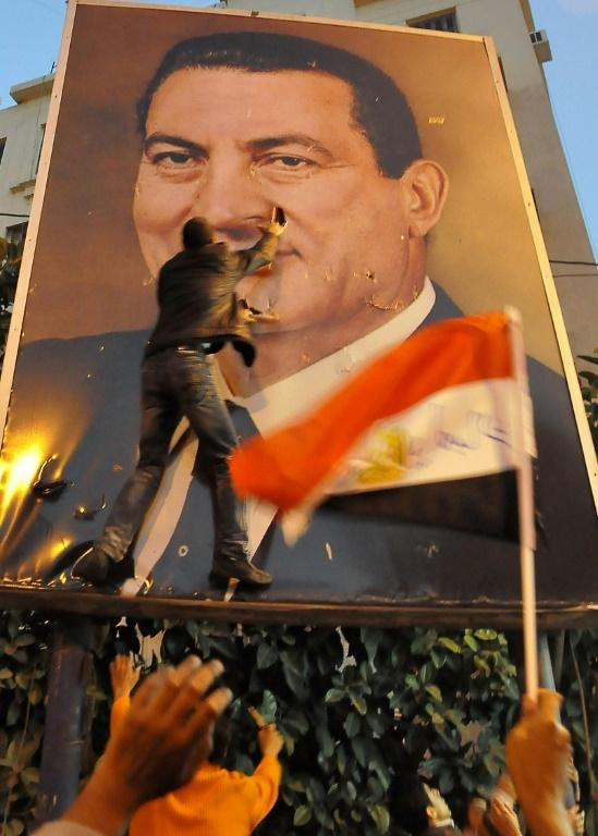 Demonstrators tear a portrait of Hosni Mubarak during a protest against his rule in the northern port city of Alexandria on January 25, 2011