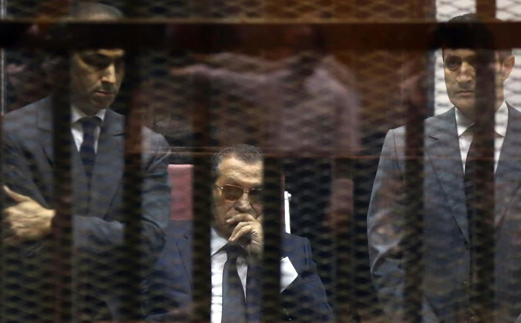 Hosni Mubarak sits in the defendant's cage between his sons during a hearing in one of his trials following his ouster in 2011