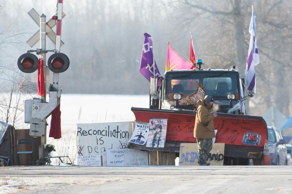 A First Nations protester walk in front of a snow plow blade that has signatures from the Wet'suwet'en hereditary chiefs as part of a train blockade in Tyendinaga, near Belleville, Ontario, Canada on February 21, 2020