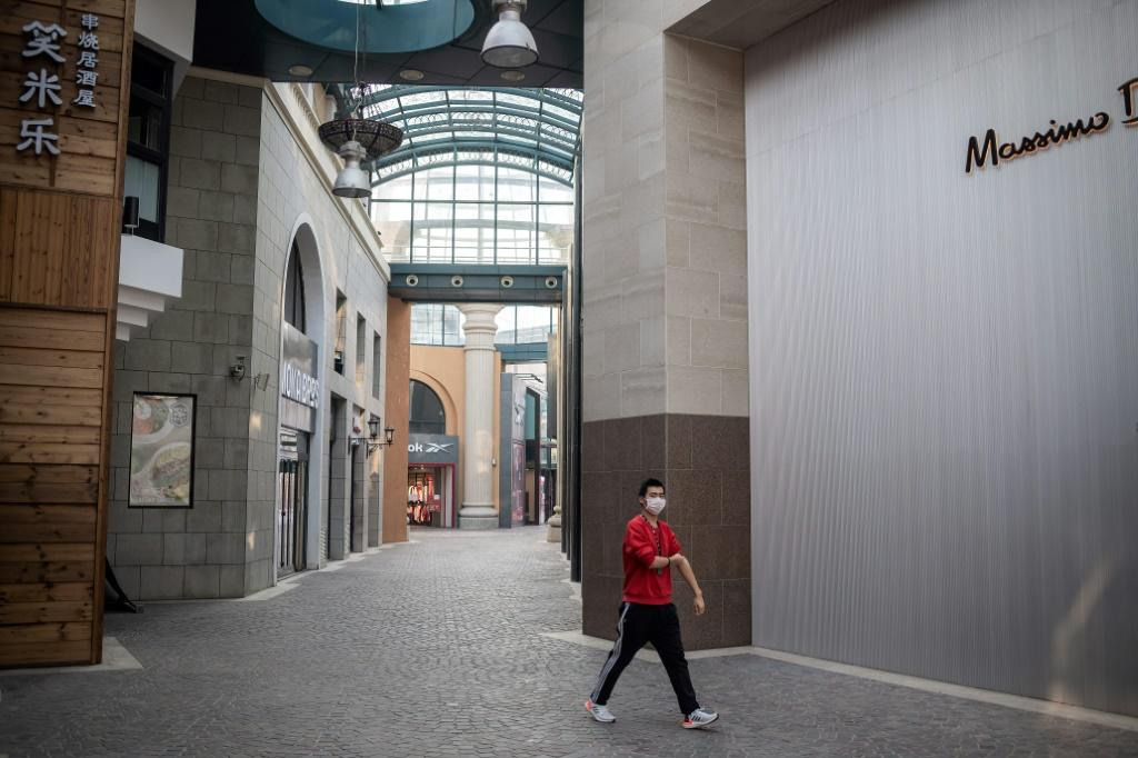 A man wearing a protective facemask, as a preventative measure against the COVID-19 coronavirus, walks through a deserted shopping mall in Beijing