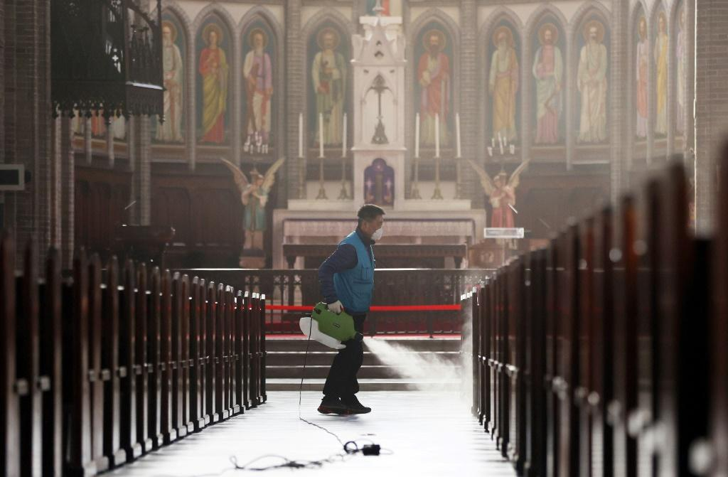 A staff member sprays disinfectant at Myeongdong Catholic Cathedral in Seoul