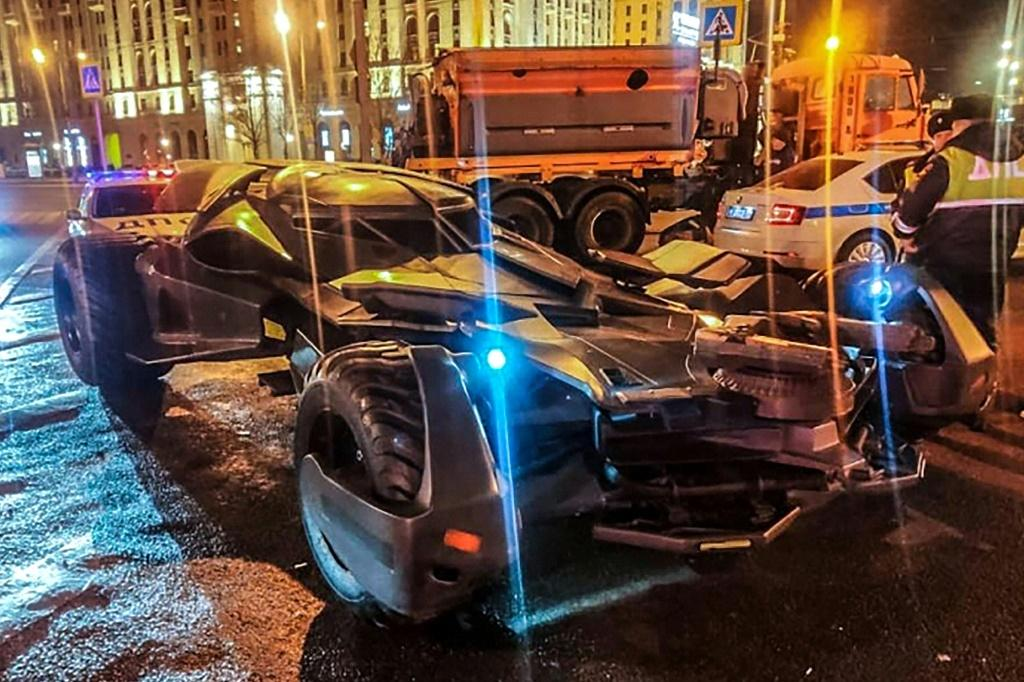 """This handout photo from Russian Interior Ministry taken on February 22, 2020 shows Russian traffic policemen standing next to a vehicle in Moscow that bears a striking resemblance to the """"Batmobile"""