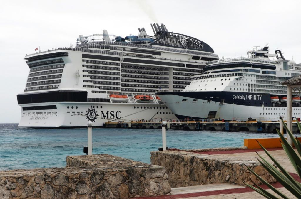 The MSC Meraviglia cruise ship (L) is seen in Cozumel, Mexico, after both Jamaica and the Cayman Islands refused to allow it to dock over fears of the new coronavirus