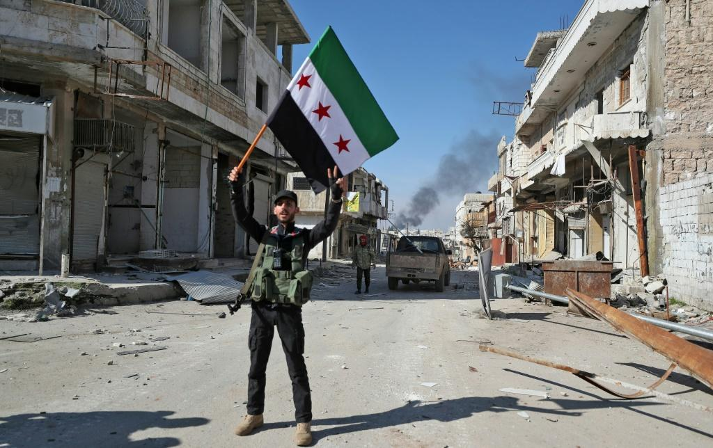 A Turkey-backed Syrian fighter celebrates in the Idlib province town of Saraqib, but the rebel counter offensive could be short-lived