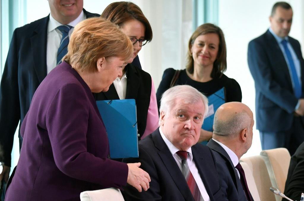 Merkel reached out to greet Horst Seehofer at a meeting on migration in Berlin