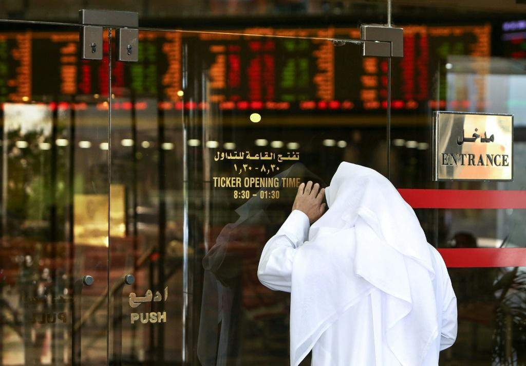 A trader checks stock prices from the outside after authorities closed the Boursa Kuwait on March 8