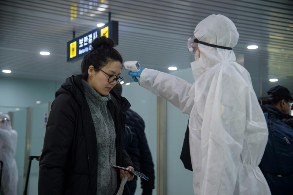 A woman has her temperature taken as foreign diplomats and embassy staff prepare to board a flight to Vladivostok at Pyongyang International Airport