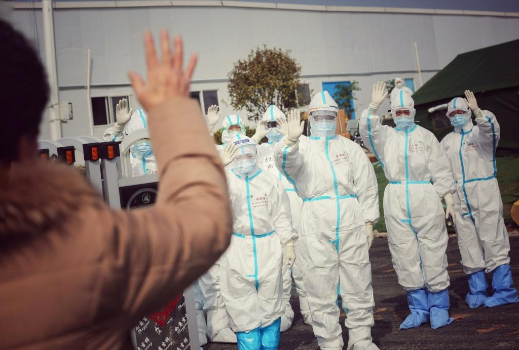 Medical staff members wave to a recovered patient at a makeshift hospital for the COVID-19 coronavirus patients in Wuhan