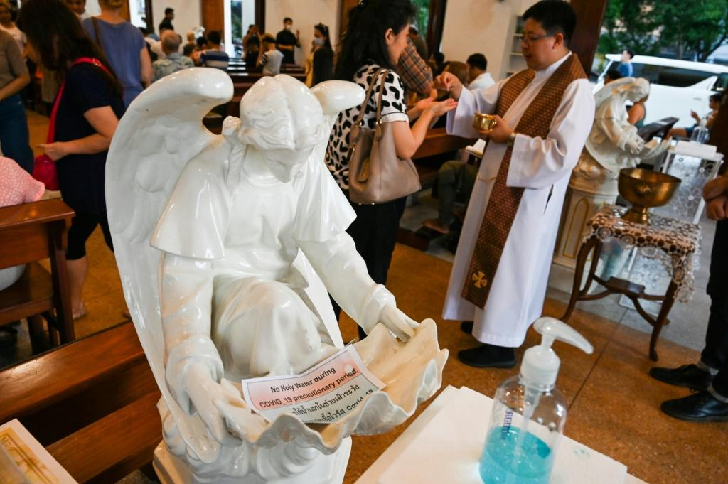 """A priest hands a holy communion in front of a statue of an angel with a sign saying """"no holy water during COVID-19 precautionary period"""" and a bottle of hand sanitiser at a church in Bangkok"""