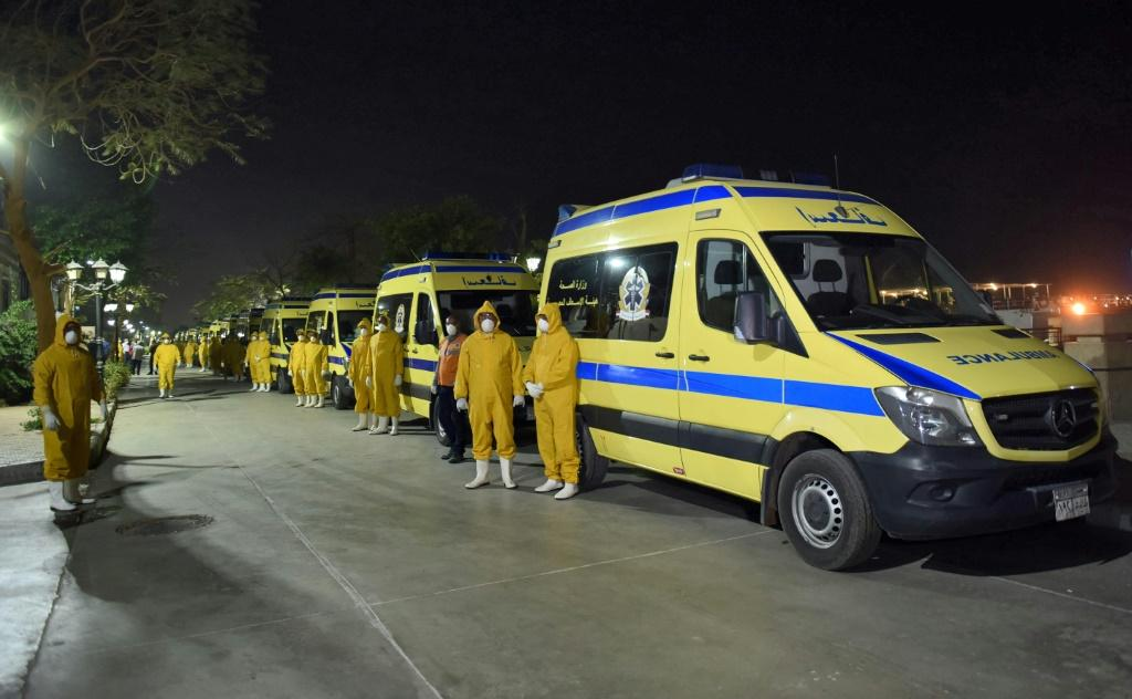 Egyptian health ministry emergency responders stand next to ambulances ready on the scene to transport suspected COVID-19 coronavirus disease cases that were detected on a Nile cruise ship