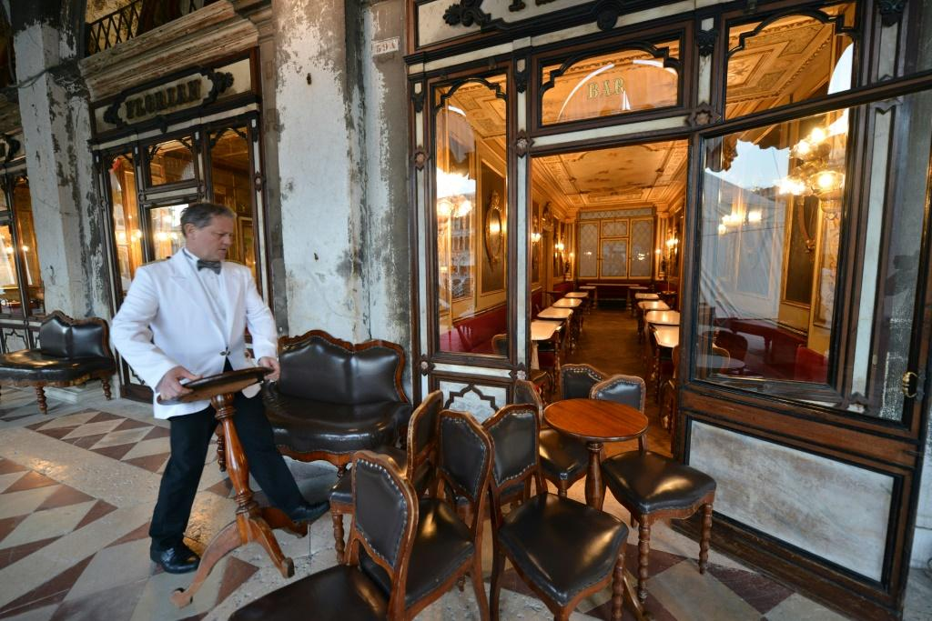 Waiters move tables and chairs inside the Cafe Florian in Saint Mark Square in Venice, after millions of people were placed under forced quarantine in northern Italy