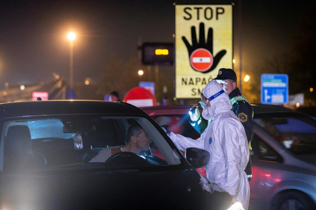 A medical worker measures body temperatures of motorists passing the Slovenian-Italian border crossing near Nova Gorica