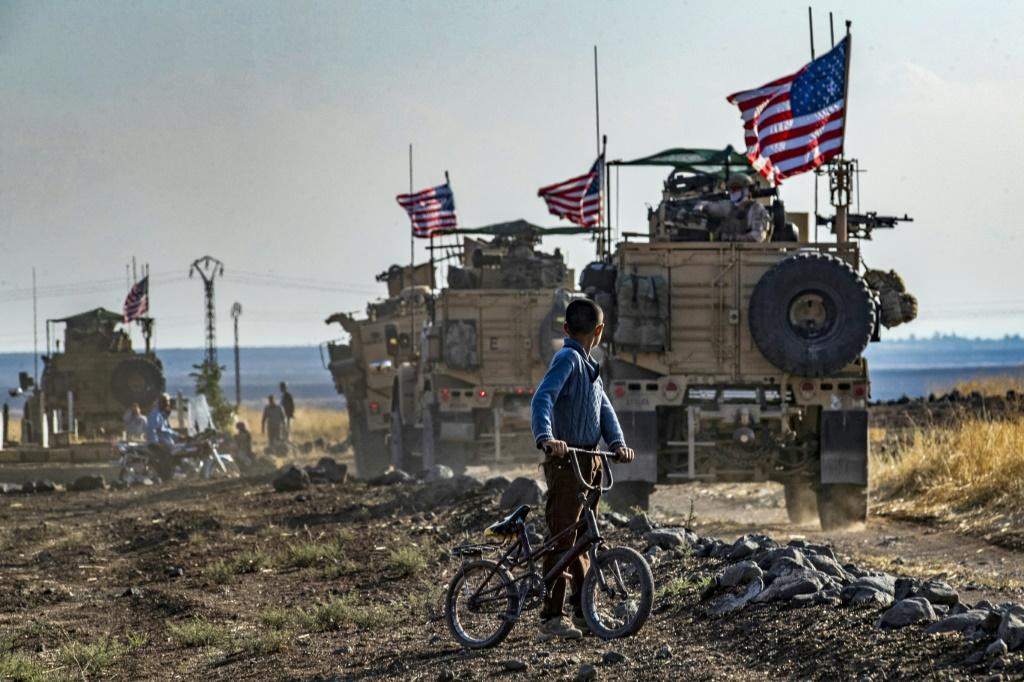 A Syrian boy watches a convoy of US armoured vehicles on patrol near the northeastern town of Qahtaniyah near the border with Turkey on October 31, 2019