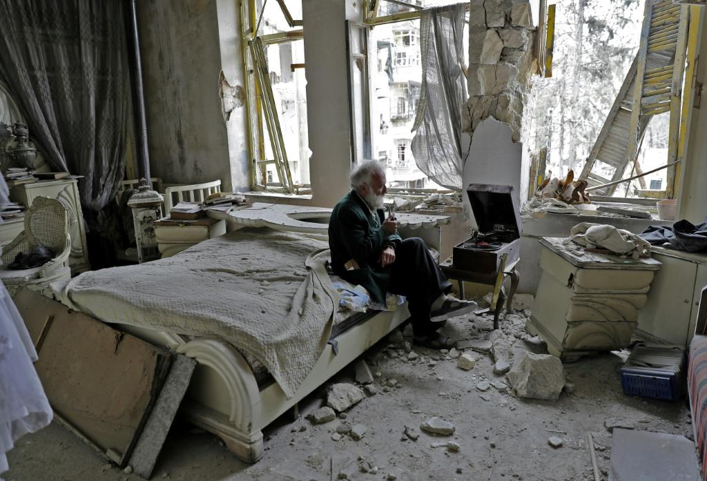 A Syrian man smokes his pipe in his destroyed bedroom in Aleppo's formerly rebel-held Shaar neighbourhood on March 9, 2017