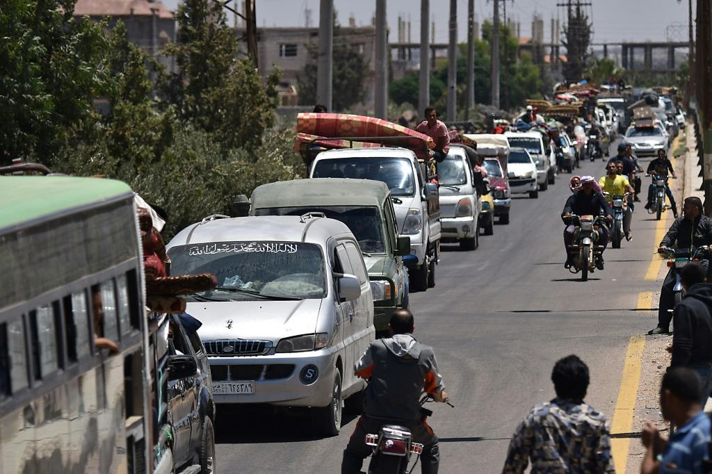 Displaced Syrians from the Daraa province travel back to their hometown in Busra, southwestern Syria, on July 11, 2018