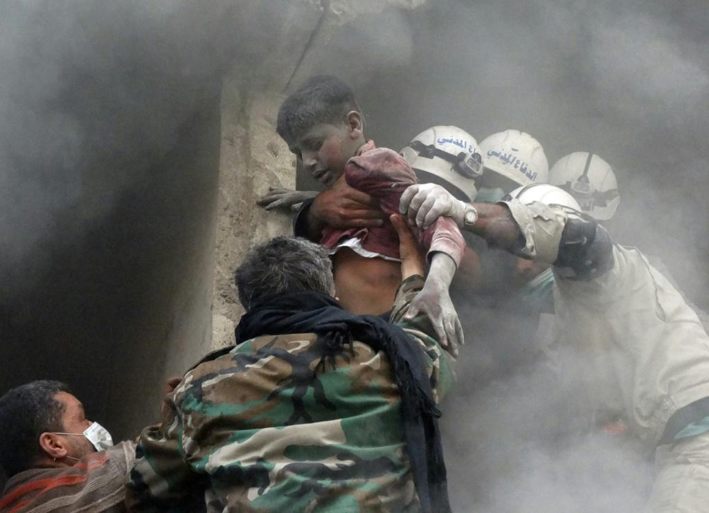 Emergency responders evacuate a Syrian boy from a residential building reportedly hit by a barrel bomb dropped by government forces in Aleppo's Shaar neighbourhood on April 6, 2014