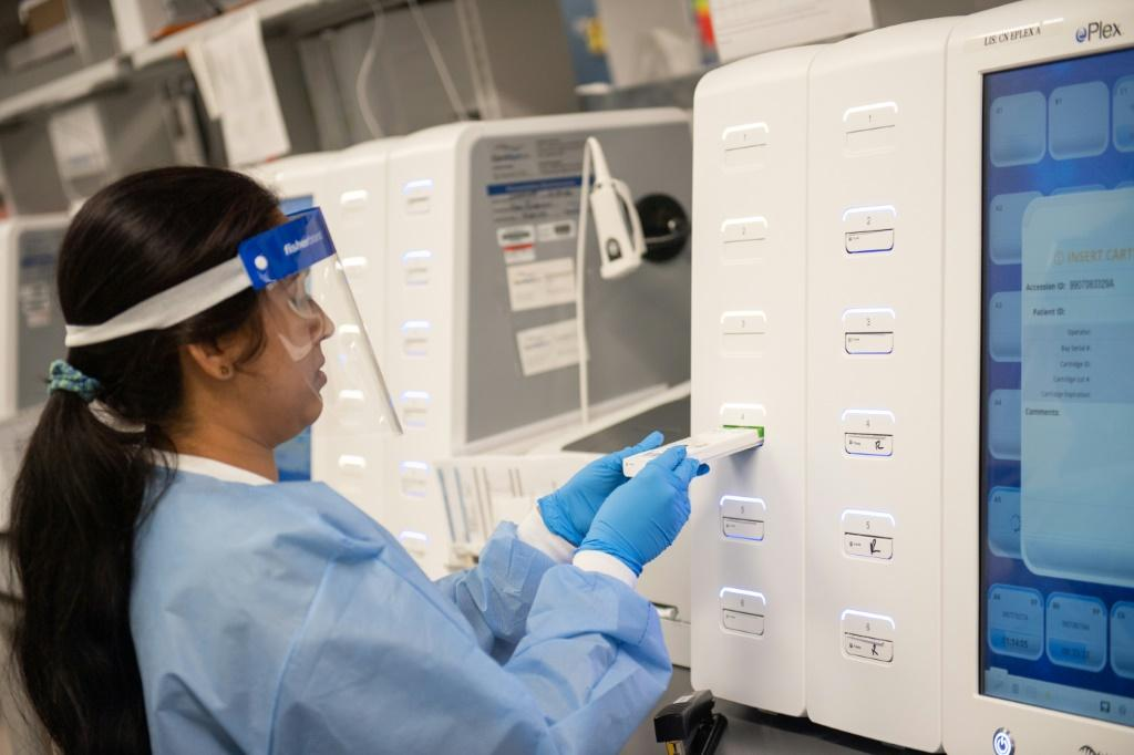 A lab technician begins semi-automated testing for COVID-19 at Northwell Health Labs in Lake Success, New York