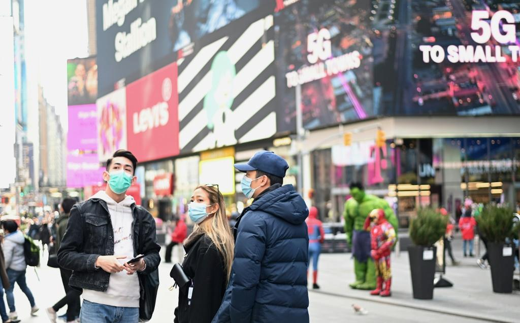 People wearing masks visit New York's Times Square on March 14, 2020