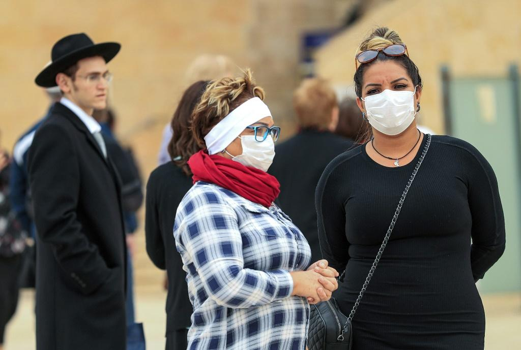 Women wearing protective masks pay a visit to the nearly deserted Western Wall, Judaism's holiest site, after Israel imposed some of the world's tightest restrictions to contain COVID-19 coronavirus disease