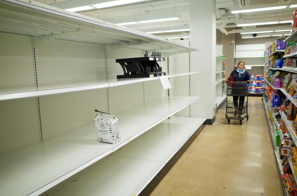 A shopper walks down an aisle with empty shelves for toilet paper at a Target store in Bethesda, Maryland on March 16, 2020