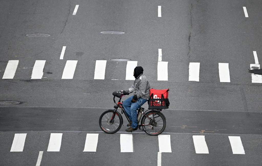 A food delivery man crosses 1st Avenue in Manhattan on March 17, 2020 in New York City