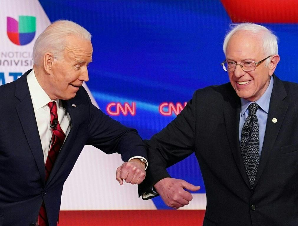 Democratic presidential hopefuls former US vice president Joe Biden (L) and Senator Bernie Sanders greet each other with a safe elbow bump before the start of the Democratic presidential debate on March 15, 2020