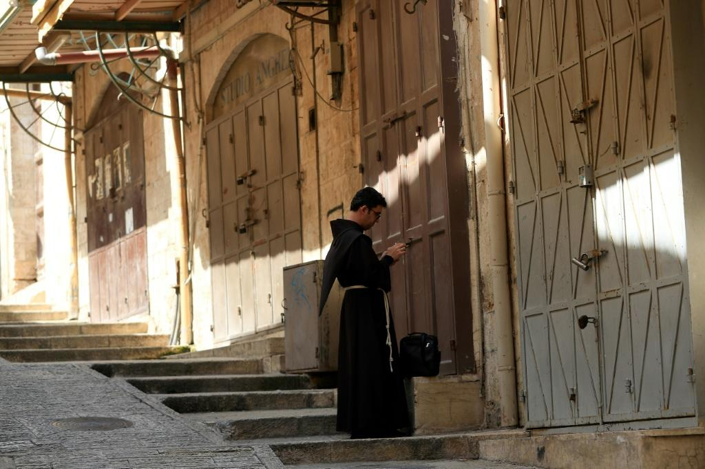 A Fransiscan friar checks his phone in the Old City of Jerusalem on March 16, 2020