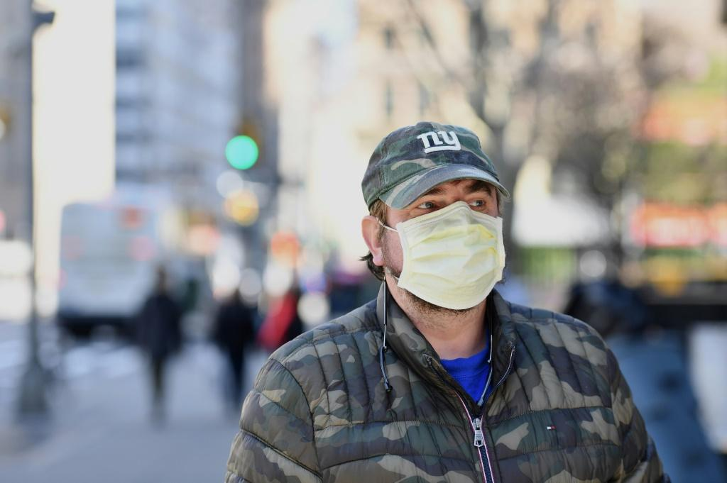 A man wearing a face mask walks in New York on March 18