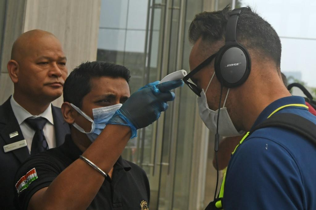 A member of hotel staff wearing a facemask amid concerns over the spread of the COVID-19 novel coronavirus checks the temperature of South African cricket player Faf du Plessis upon his arrival at a hotel in Kolkata