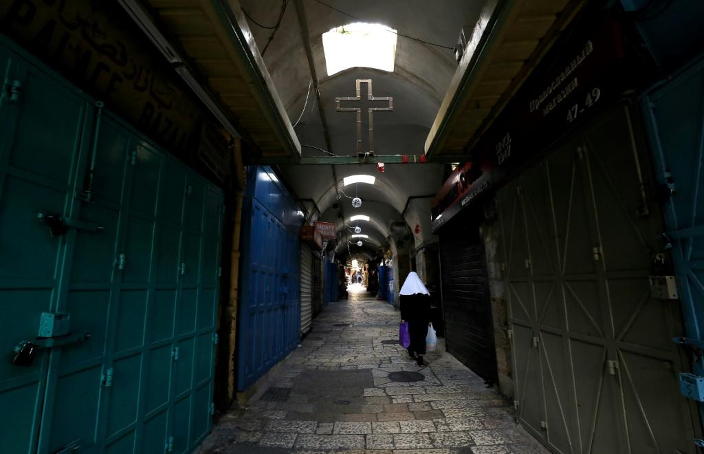 A woman walks past closed shops along a deserted alley in the Old City of Jerusalem