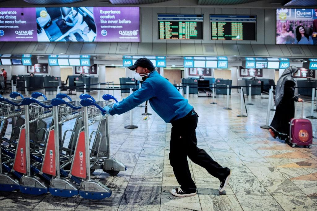 An airport employee wears a face mask as a preventive measure against the COVID-19 coronavirus at the O.R. Tambo international airport in Johannesburg