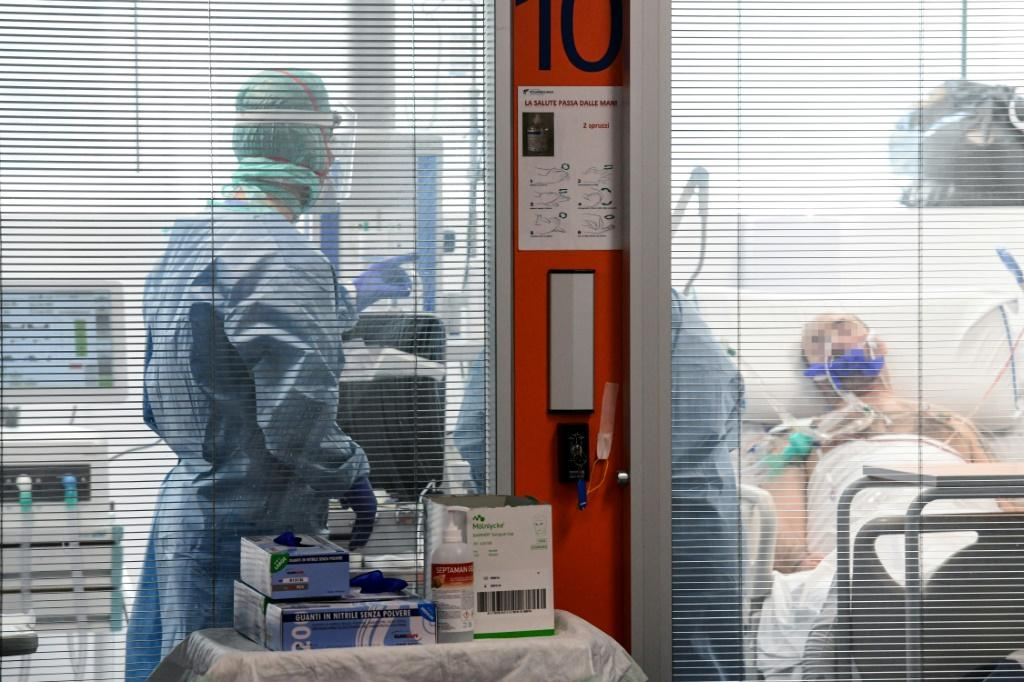 Medical workers wearing a face make and protection gear tend to a patient inside the new coronavirus intensive care unit of the Brescia Poliambulanza hospital as the town saw the country's highest daily rise in case numbers