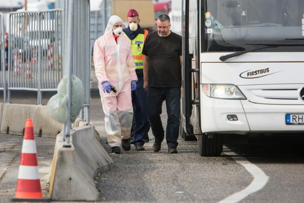 Hungarian police and medics control passengers on a bus at the border -- huge tailbacks have ensued since Budapest shut its borders Monday, albeit the rules seemed to be being applied arbitrarily in at least some cases
