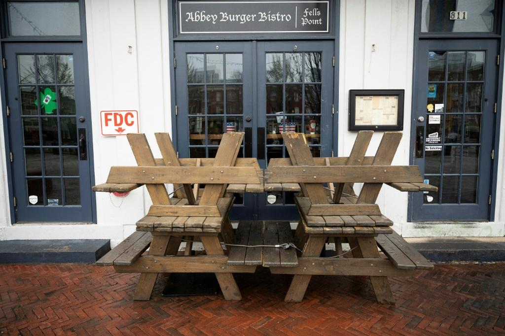 Picnic tables block the closed doors of Abbey burger Bistro in Baltimore, after Maryland Governor Larry Hogan banned on-premise drinking and dining at restaurants