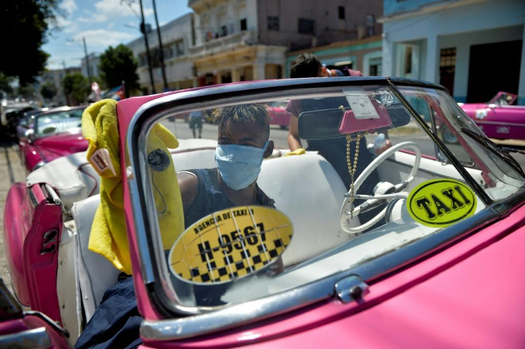 Workers of a private taxi company disinfect old American cars wearing face masks as a preventive measure against the spread of the new coronavirus