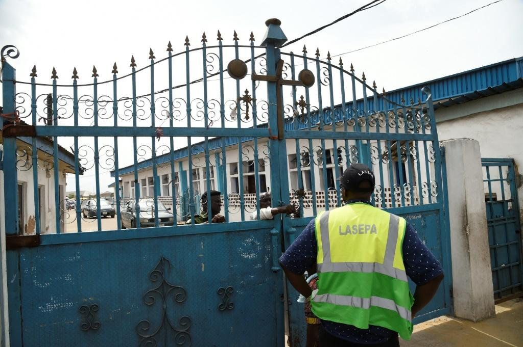 Worshippers clustered at the gate of Makoko's Celestial Church of Christ only to find policemen handing out fliers on the dangers of the virus