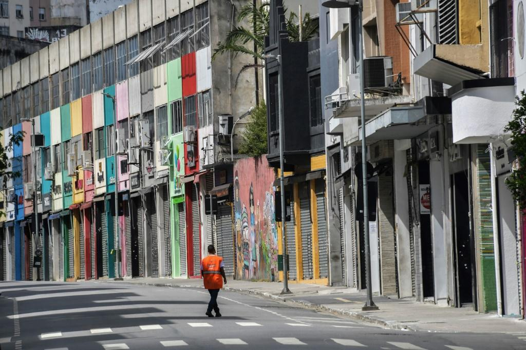 A man walks on a popular shopping street in downtown Sao Paulo on March 24