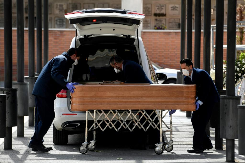 Mortuary employees wearing face masks wheel a coffin into the crematorium of La Almudena cemetery in Madrid during the funeral of a COVID-19 coronavirus victim