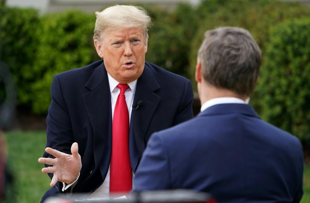 US President Donald Trump (L) speaks with anchor Bill Hemmer during a Fox News virtual town hall meeting from the Rose Garden of the White House in Washington, DC, on March 24, 2020