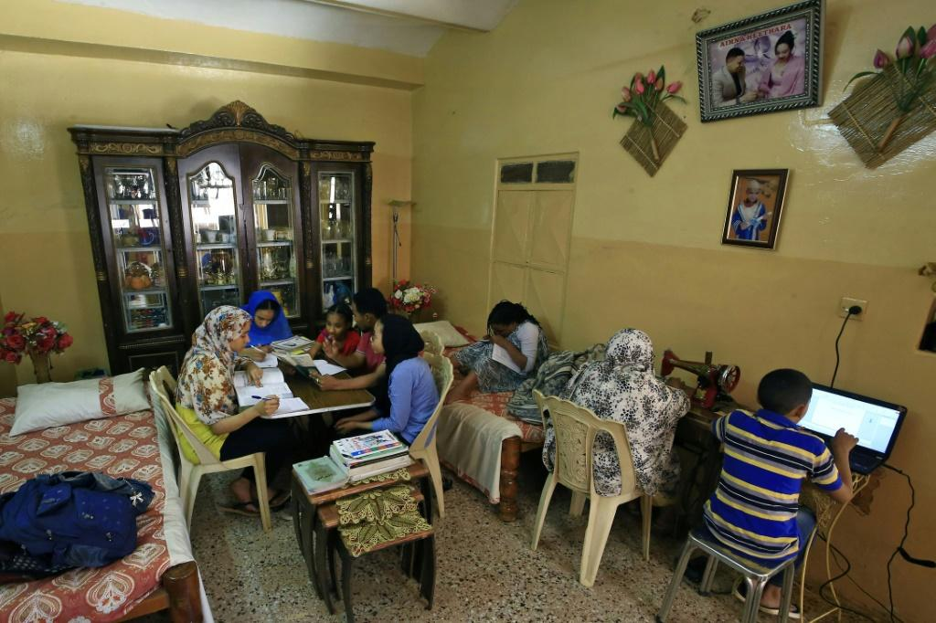 A family studies together at home in Khartoum