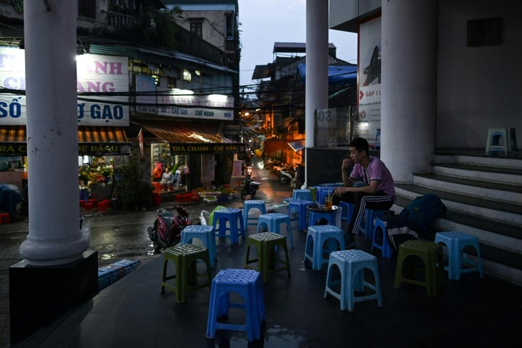 A man sits alone at a street-cafe, amid concerns over the spread of the COVID-19 novel coronavirus, in Hanoi