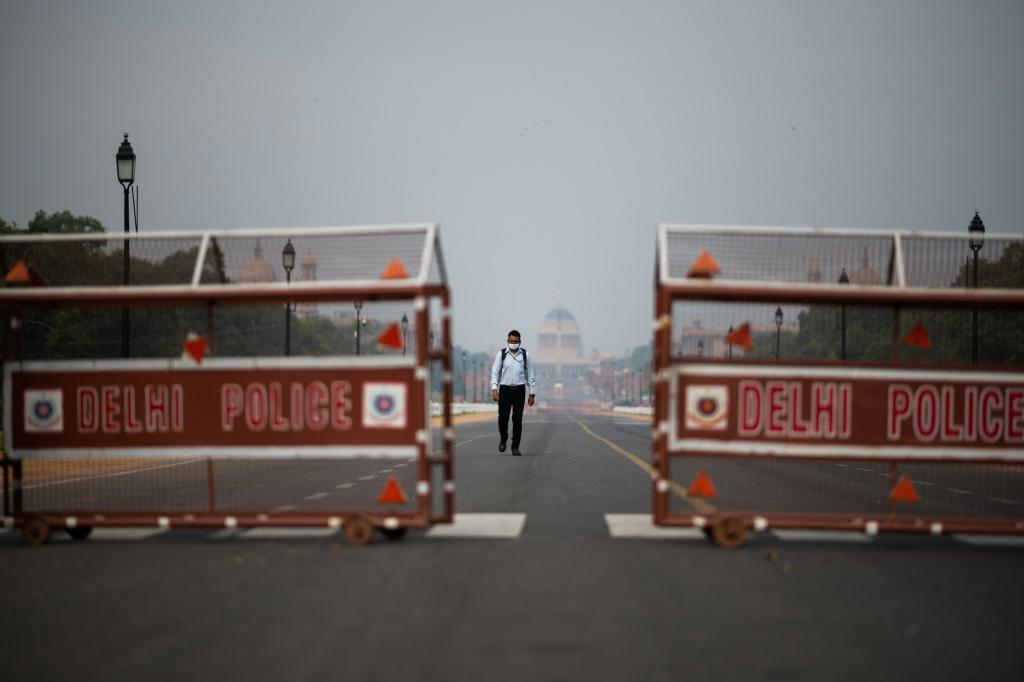 A man walks on a deserted road in New Delhi during an Indian government-imposed lockdown against COVID-19
