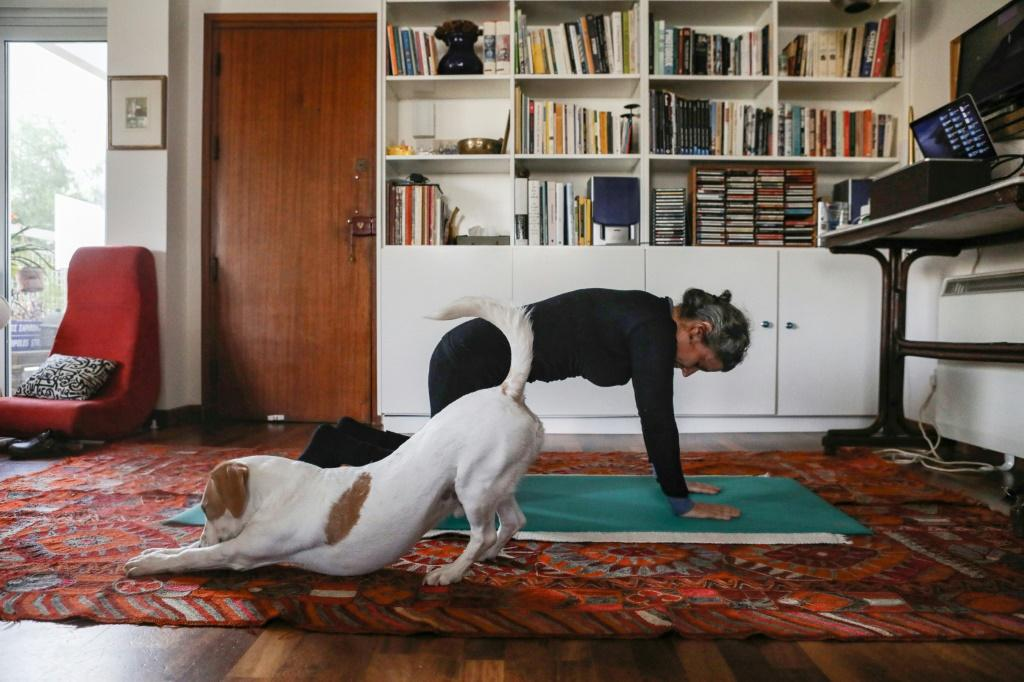 A woman follows an online pilates class at home, as her dog Elvis stretches next to her