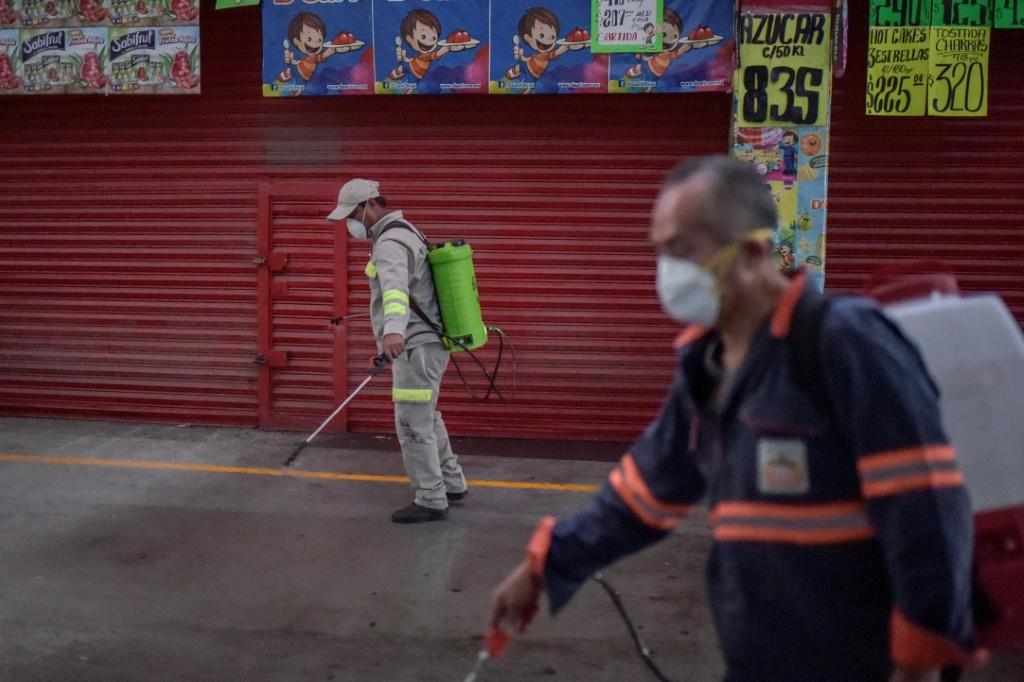 "Cleaning personnel spray disinfectant at the ""Central de Abasto"" Mexico City's giant food wholesale market"