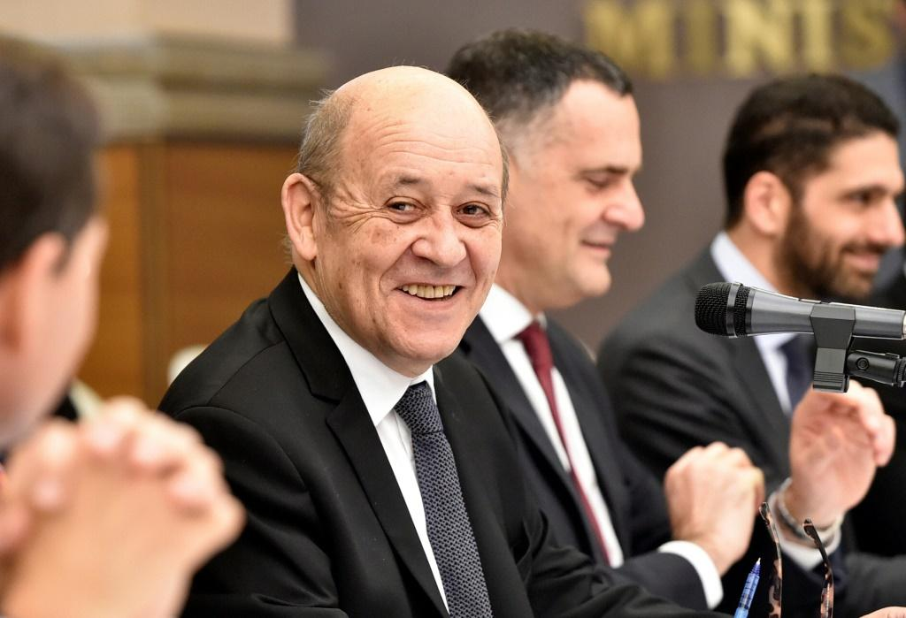 """French Foreign Minister Jean-Yves Le Drian, seen here on a March 12, 2020 visit to Algeria, has warned not to """"exploit"""" the coronavirus pandemic"""