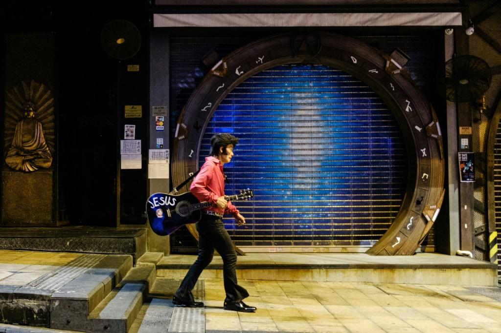 """Kwok Lam-sang, who has been performing covers of Elvis Presley songs under the name of """"Melvis"""" since 1992, walks with his guitar past closed bars in the usually busy drinking area of Lan Kwai Fong in Hong Kong"""