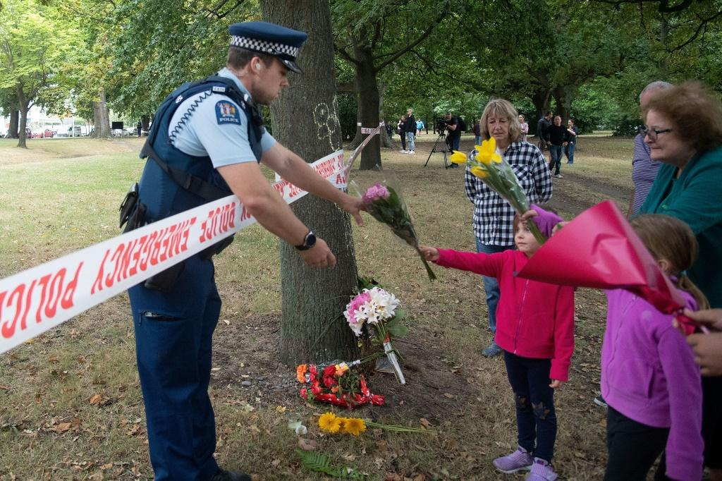 Members of the public hand flowers to a police officer to take over to the Dean Avenue mosque March 17, 2019 in Christchurch, New Zealand