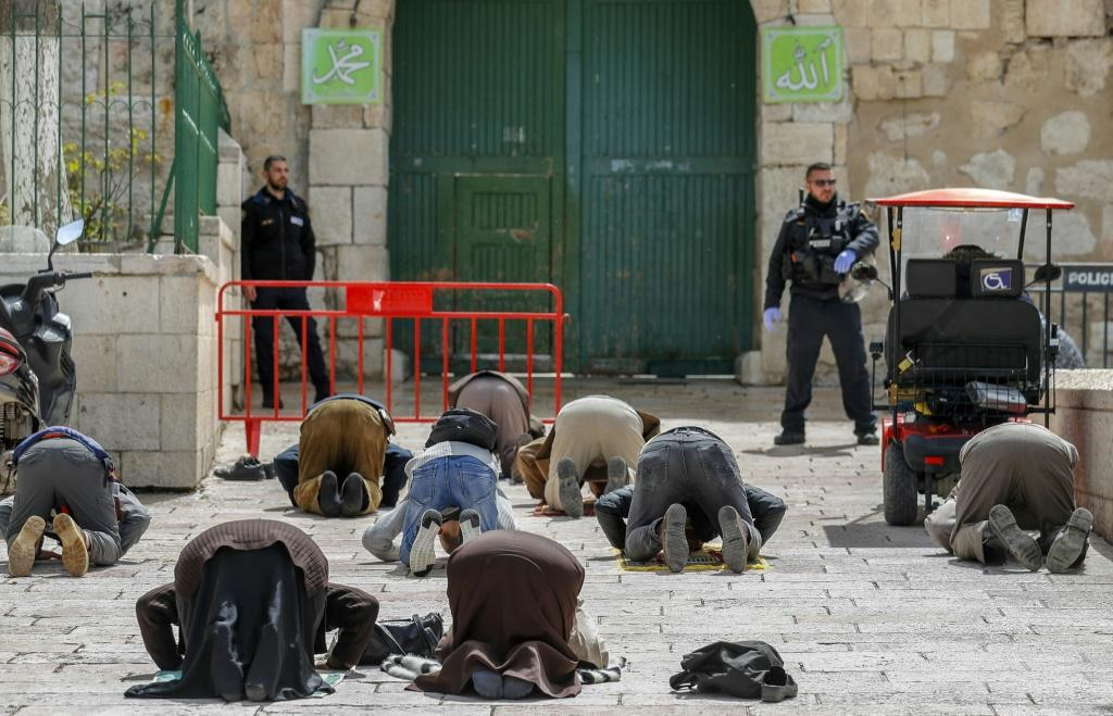 Palestinian Muslim men in prayer near the gate of the Al-Aqsa mosque compound, closed as part of preventive measures against the spread of the coronavirus
