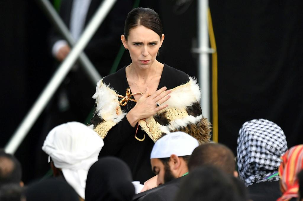 Prime Minister of New Zealand Jacinda Ardern places her hand over her heart as she walks past a family who lost members in the mosque attacks of 2019