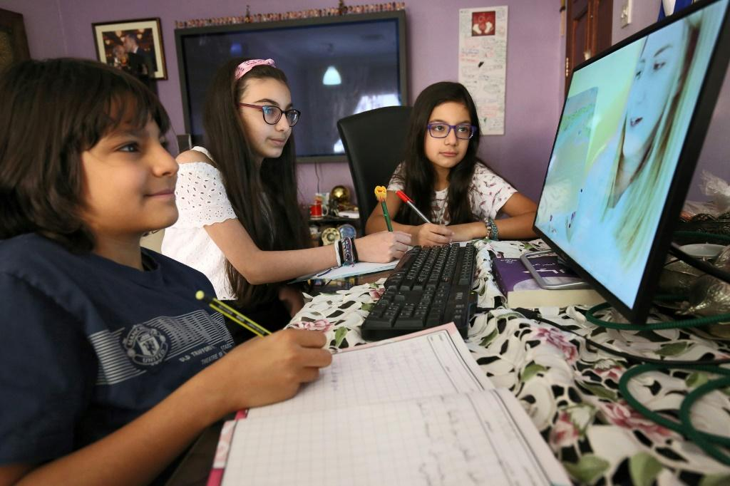 Students attend an online class at home in Kuwait City